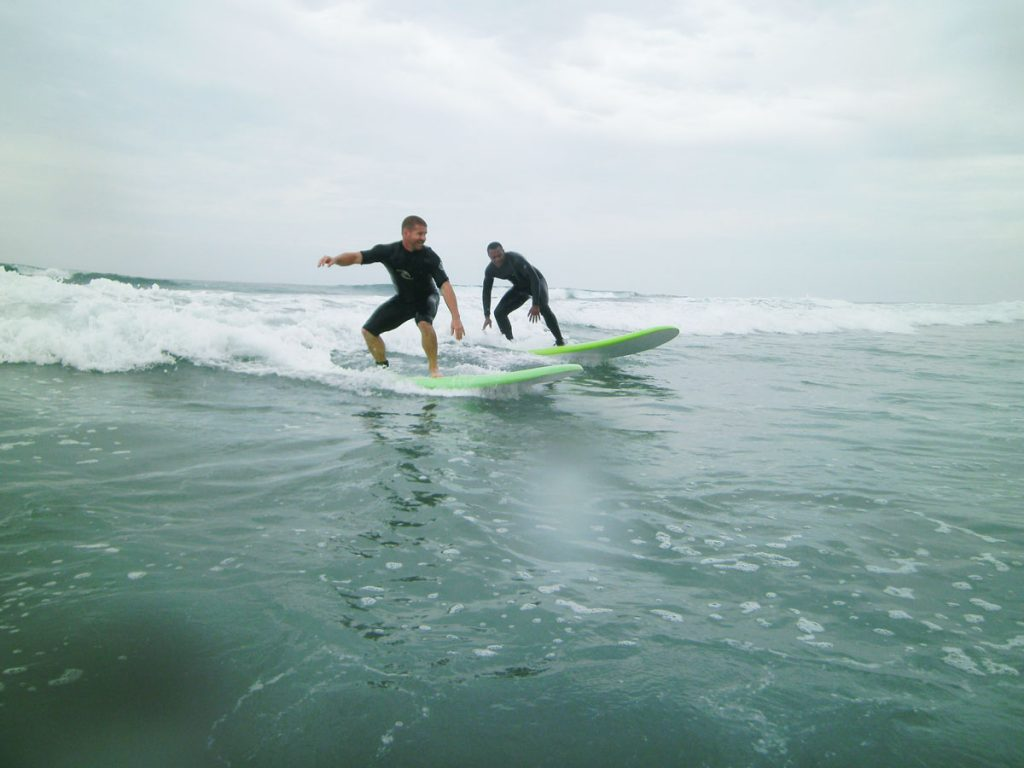Two Marines surfing at an Outdoor Adventure event
