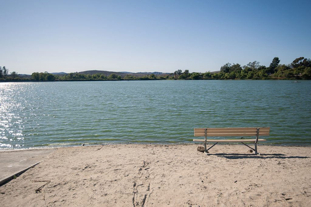 A view of the lake with a bench in the foreground.