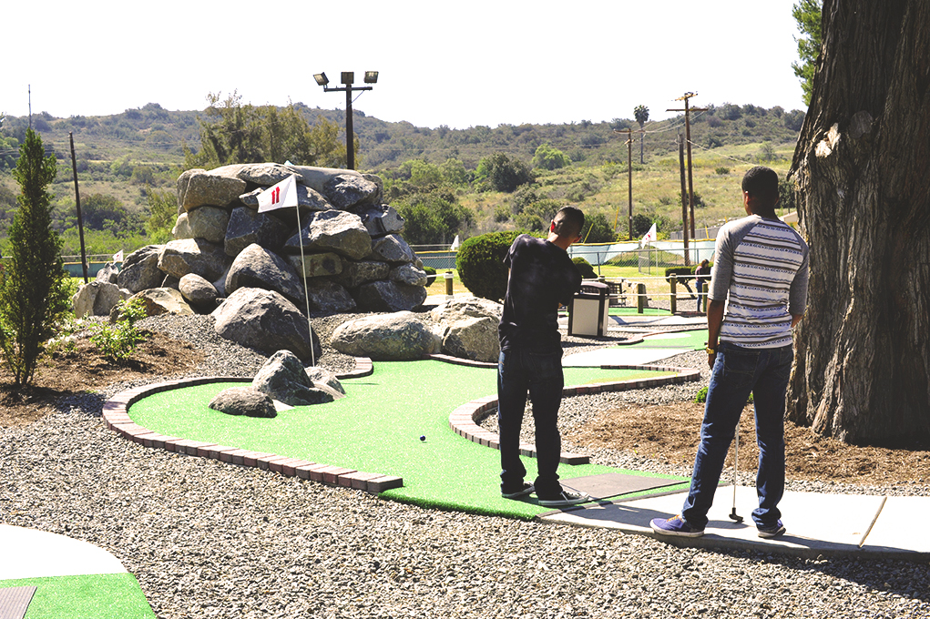 Two marines on the green at miniature golf course, view from behind
