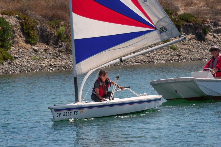 Student learning to sail in the marina on a boat