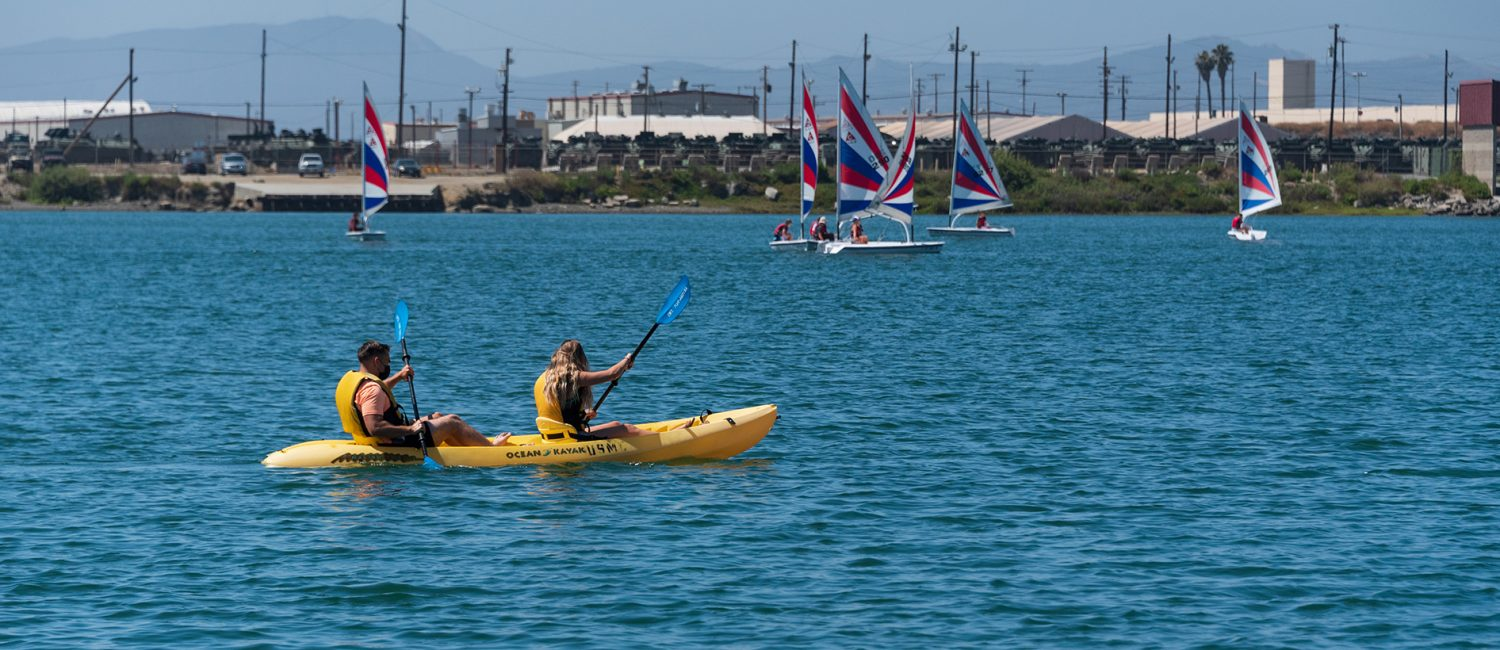 Couple kayak in water near sailboats
