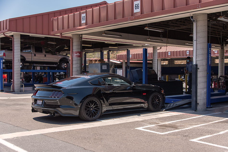 black mustang parked by stall at auto skills
