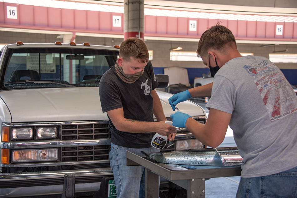 two marines working on vehicle at auto skills