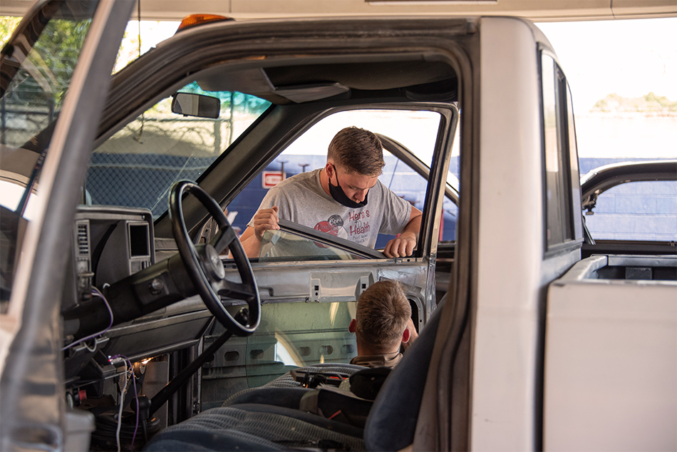 two marines fixing truck window at auto skills