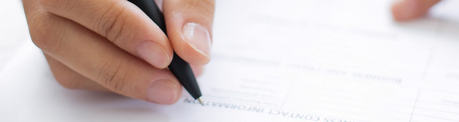 Closeup of hand writing on Form