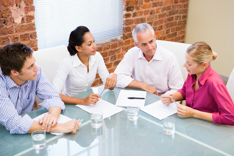 Four business employees sitting having a meeting.
