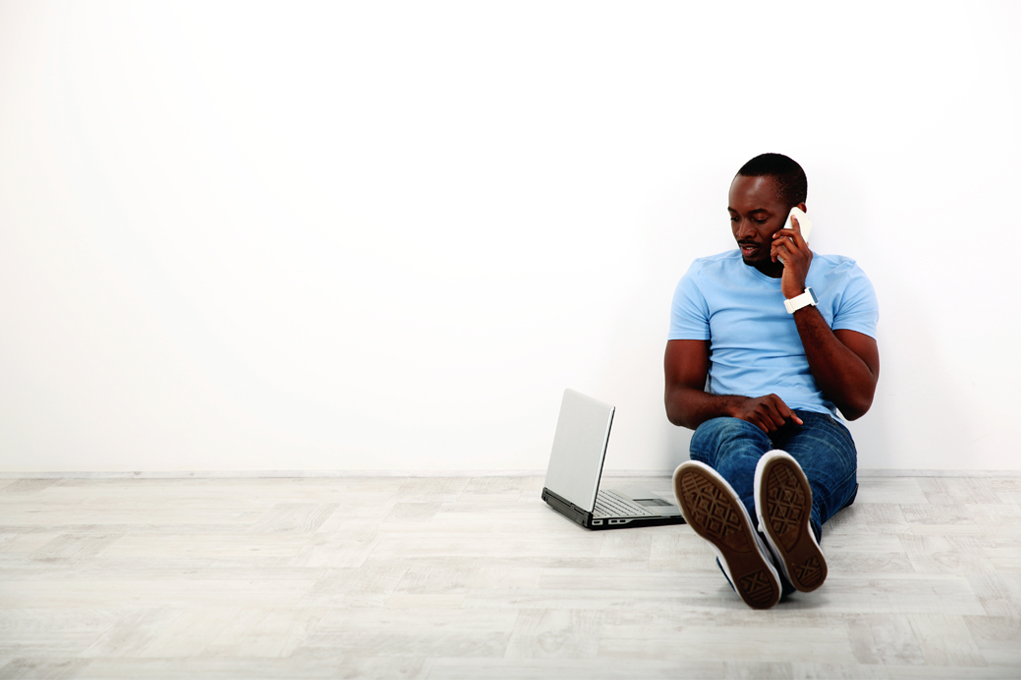 Person sitting on the floor with a laptop, on the phone.